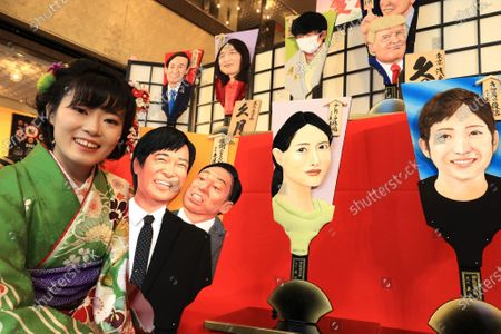 "Stock Image of Japanese doll maker Kyugetsu employee in kimono displays ornamental wooden rackets ""hagoita"" decorated with depiction of actors Masato Sakai with Teruyuki Kagawa (L), actress Satomi Ishihara (C) and young female swimmer Rikako Ikee (R) at the company's showroom in Tokyo on Thursday, December 3, 2020. The company made special hagoitas for this year's news makers as yearend tradition."