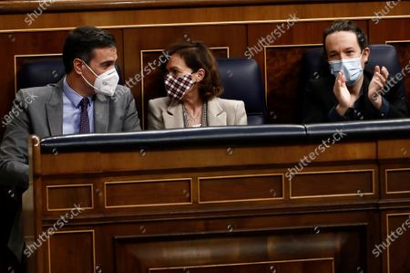 (L-R) Spanish Prime Minister, Pedro Sanchez, chats with his First Deputy PM, Carmen Calvo, next to Second Deputy PM, Pablo Iglesias, during a debate on 2021 National Budget bill at Congress of Deputies in Madrid, Spain, 03 December 2020. It is expected the National Budget bill will be passed with an absolute majority at Lower Chamber after the agreements reached by central government with several other political parties.