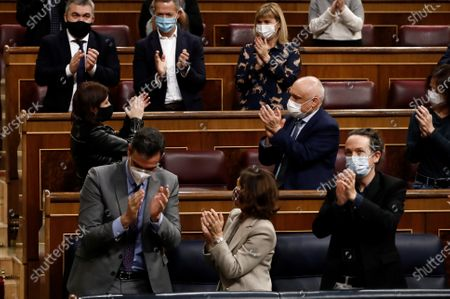 (L-R, front) Spanish Prime Minister, Pedro Sanchez, his First Deputy PM, Carmen Calvo, and Second Deputy PM, Pablo Iglesias, applaud during a debate on 2021 National Budget bill at Congress of Deputies in Madrid, Spain, 03 December 2020. It is expected the National Budget bill will be passed with an absolute majority at Lower Chamber after the agreements reached by central government with several other political parties.
