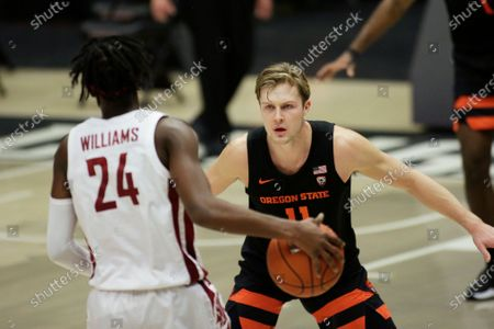 Oregon State guard Zach Reichle (11) defends Washington State guard Noah Williams (24) during the second half of an NCAA college basketball game in Pullman, Wash