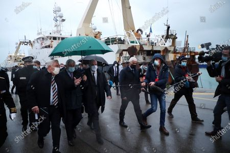 French Prime Minister Jean Castex (C), flanked by Mayor of Boulogne sur Mer Frederic Cuvillier (L) meets with local authorities and different actors of the fishing port of Boulogne-sur-mer during a visit on the preparations ahead of the end of the Brexit transition period on 31 December 2020, in Boulogne sur Mer, France, 03 December 2020.
