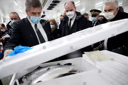 French Prime Minister Jean Castex, center, flanked by mayor of Boulogne-sur-Mer Frederic Cuvillier, right, meets with different actors of the fishing port of Boulogne-sur-Mer, northern France, during a visit on the preparations ahead of the end of the Brexit transition period, Thursday, Dec.3 2020. The British government told businesses on Tuesday to make sure they are ready for big changes when the U.K. makes its final Brexit break from the European Union in lees than a month. But with negotiations on a free-trade deal with the bloc stuck, firms say they still don't know key details of what those changes will be