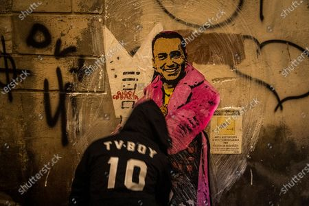 Stock Image of The street artist Tvboy at work in the night, the artwork 'Giggiebbasta' depicts the Italian Minister of Foreign Affairs Luigi Di Maio as the Italian rapper Sfera e Ebbasta