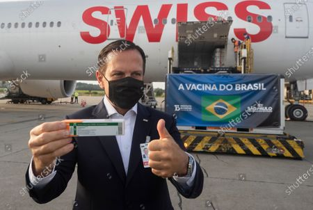 Sao Paulo Gov. Joao Doria poses for photo flashing a thumbs up next to a container carrying the experimental COVID-19 vaccine CoronaVac after it was unloaded from a cargo plane that arrived from China at Guarulhos International Airport in Guarulhos, near Sao Paulo, Brazil Brazil