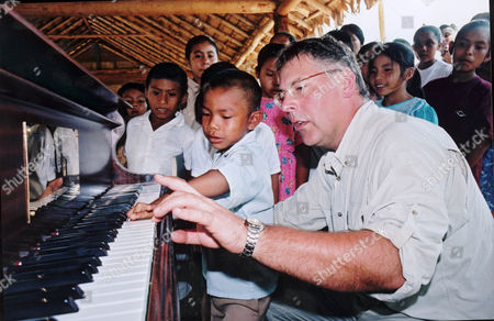 Dr Simon Richards plays the piano watched by Knang (age 5) and other children