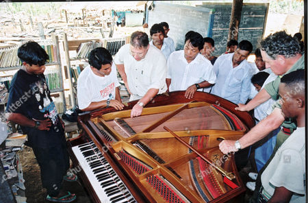 Stock Image of Dr Simon Richards checks the strings of the piano as Wai-Wai villagers look on