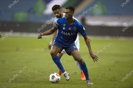 Al-Hilal's player Mohamed Kanno (front) in action against Al-Fateh's Mohammed Al Saeed (back) during the Saudi Professional League soccer match between Al-Hilal and Al-Fateh at King Fahd International Stadium, in Riyadh, Saudi Arabia, 03 December 2020.