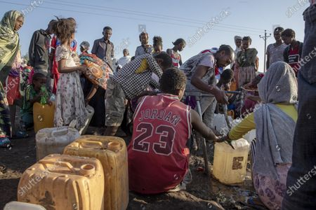 Tigray refugee who fled the conflict in the Ethiopia's Tigray, wearing a Michael Jordan jersey, fills his gallon with water at Hamdeyat Transition Center near the Sudan-Ethiopia border, eastern Sudan, . Ethiopian forces on Thursday blocked people from the country's embattled Tigray region from crossing into Sudan at the busiest crossing point for refugees, Sudanese forces said