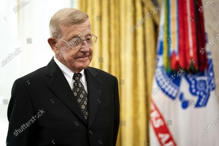 Former football coach Lou Holtz listens as United States President Donald J. Trump makes remarks before presenting the Medal of Freedom to him, in the Oval Office,.