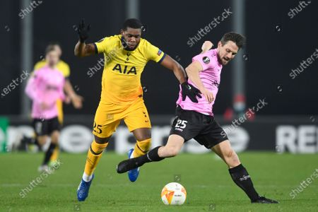 Tottenham's Japhet Tanganga, left, challenges for the ball with LASK's James Holland during the Europa League Group J soccer match between Linzer ASK and Tottenham Hotspur at the Linzer stadium in Linz, Austria