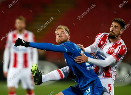 Hoffenheim's Klauss, centre, duels for the ball with Red Star's Milos Degenek during the Europa League group L soccer match between Red Star and Hoffenheim at the Rajko Mitic Stadium in Belgrade, Serbia