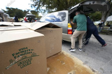 Workers load boxes of food into cars during a food distribution event, at Amelia Earhart Park in Hialeah, Fla. The event, which provided enough food for 1200 families, was put on by Miami-Dade Parks, Recreation and Open Spaces, and Feeding South Florida