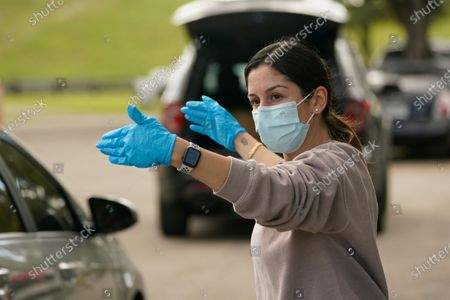 Stock Photo of Bianca Gonzalez directs cars during a food distribution event, at Amelia Earhart Park in Hialeah, Fla. The event, which provided enough food for 1200 families, was put on by Miami-Dade Parks, Recreation and Open Spaces, and Feeding South Florida