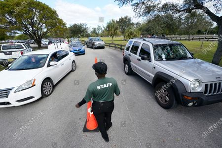 Monica, who declined to give her last name, directs cars during a food distribution event, at Amelia Earhart Park in Hialeah, Fla. The event, which provided enough food for 1200 families, was put on by Miami-Dade Parks, Recreation and Open Spaces, and Feeding South Florida