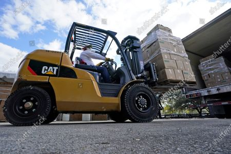 Stock Image of Forklift driver unloads a truck full of food to be given out, at Amelia Earhart Park in Hialeah, Fla. The event, which provided enough food for 1200 families, was put on by Miami-Dade Parks, Recreation and Open Spaces, and Feeding South Florida
