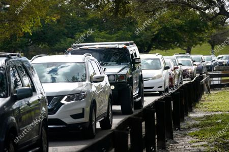 Stock Picture of Cars line up during a food distribution event, at Amelia Earhart Park in Hialeah, Fla. The event, which provided enough food for 1200 families, was put on by Miami-Dade Parks, Recreation and Open Spaces, and Feeding South Florida