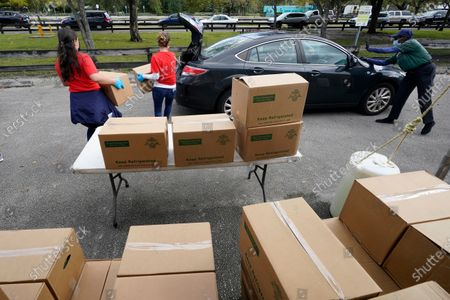 Workers load boxes of food into a car during a food distribution event, at Amelia Earhart Park in Hialeah, Fla. The event, which provided enough food for 1200 families, was put on by Miami-Dade Parks, Recreation and Open Spaces, and Feeding South Florida