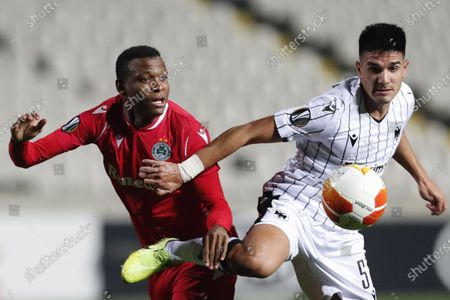 Stock Image of Omonia's Shehu Abdullahi, left, fights for the ball with PAOK's Charis Tsingaras during the Europa League group E soccer match between Omonia and PAOK at GSP stadium in Nicosia, Cyprus