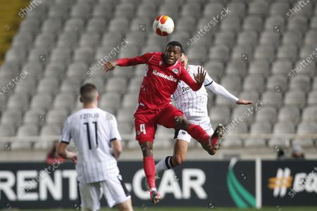 Stock Photo of Omonia's Shehu Abdullahi, center front, jumps for ball with PAOK's Rodrigo Soares during the Europa League group E soccer match between Omonia and PAOK at GSP stadium in Nicosia, Cyprus