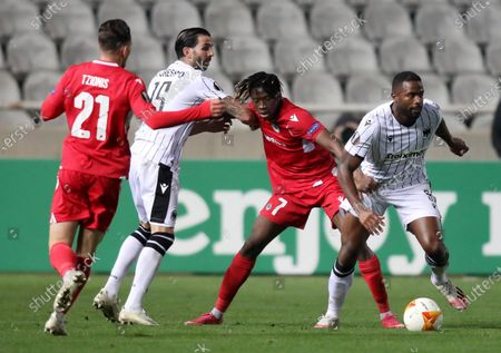 Fernando Varela (R) and Jose Angel Crespo (2L) of PAOK in action against Kaly Sene (2R) and Marinos Tzioni (L) of Omonoia Nicosia during the UEFA Europa League group E soccer match between Omonoia Nicosia and PAOK FC at the GSP stadium in Nicosia, Cyprus, 03 December 2020.