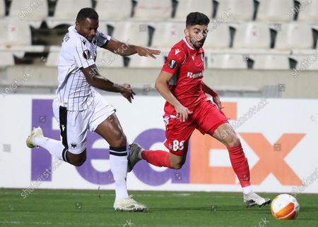 Stock Photo of Andronikos Kakoulli (R) of Omonoia Nicosia in action against Fernando Varela (L) of PAOK during the UEFA Europa League group E soccer match between Omonoia Nicosia and PAOK FC at the GSP stadium in Nicosia, Cyprus, 03 December 2020.