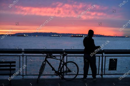 Stock Photo of A man watches the sunset over New York Harbor from Louis Valentino, Jr. Park in the Red Hook neighborhood of Brooklyn.