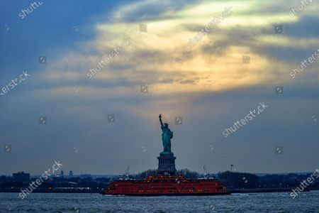 A Staten Island Ferry passes in front of the Statue of Liberty in New York Harbor as seen from Louis Valentino, Jr. Park in the Red Hook neighborhood of Brooklyn.