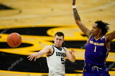 Iowa guard CJ Fredrick (5) passes ahead of Western Illinois guard Anthony Jones (1) during the first half of an NCAA college basketball game, in Iowa City, Iowa