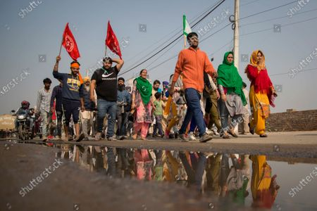 """Group of protesters shout slogans as they arrive to join farmers demanding to abolish new farming laws they say will result in exploitation by corporations, eventually rendering them landless, at the Delhi-Haryana state border, India, . The busy, nonstop, arterial highways that connect most northern Indian towns to this city of 29 million people, now beat to the rhythm of never-heard-before cries of """"Inquilab Zindabad"""" (""""Long live the revolution""""). Tens and thousands of farmers, with colorful distinctive turbans and long, flowing beards, have descended upon its borders where they commandeer wide swathes of roads"""