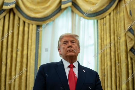 President Donald Trump listens during a ceremony to present the Presidential Medal of Freedom to former football coach Lou Holtz, in the Oval Office of the White House, in Washington