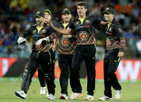 Australia's Moises Henriques, second right, celebrates with teammates after taking the wicket of India's Hardik Pandya during their T20 international cricket match at Manuka Oval, in Canberra, Australia