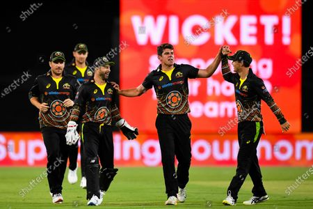 Moises Henriques of Australia (C) celebrates with team mates after claiming the wicket of Hardik Pandya of India during the first T20 cricket match between Australia and India at Manuka Oval in Canberra, Australia, 04 December 2020.