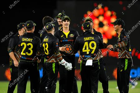 Moises Henriques (C) of Australia celebrates with team mates after claiming the wicket of Hardik Pandya of India during the first T20 cricket match between Australia and India at Manuka Oval in Canberra, Australia, 04 December 2020.