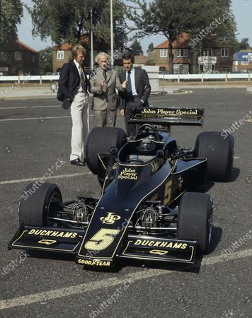 Ronnie Peterson, Colin Chapman and Jacky Ickx look over the new car, portrait.  World Copyright: LAT Photographic.