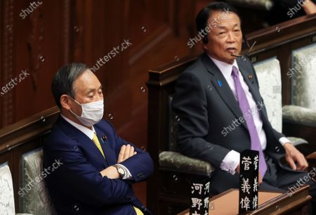 Japanese Prime Minister Yoshihide Suga (L) and Finance Minister Taro Aso attend Lower House's plenary session at the National Diet in Tokyo on Friday, December 4, 2020. An extraordinary Diet session will close on December 5 and an ordinary session will open the middle of next month.
