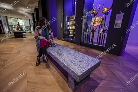 Stock Photo of Jenny Holzer's artwork - For Science - in Medicine: The Wellcome Galleries of the Science Museum - marking a year since the opening of that gallery and the re-opening of the Museum after the second covid 19 lockdown. The work comprises two benches that offer a place of respite and reflection in the gallery. . Constructed from Silver Cloud granite, the benches are inscribed with words from two writers who experienced medical treatment: Susan Sontag and Paul Kalanithi. The texts are taken from Sontag's Illness as Metaphor from 1978 - 'Illness is the night-side of life' - and Kalanithi's When Breath Becomes Air from 2016 - 'What kind of life exists without language?'.