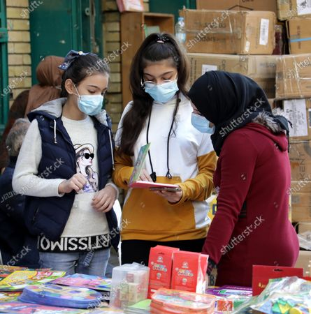Young girls wear face masks as they shop at the weekly books market at Al-Mutanabbi Street in central Baghdad, Iraq, 04 December 2020. Iraq needs international assistance to enact its plan to provide its citizens with a free-of-charge Covid-19 vaccine, Iraqi President Barham Salih told the United Nations on 03 December 2020.