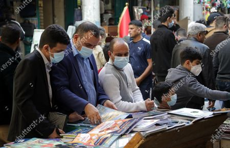People wear face masks as they shop at the weekly books market at Al-Mutanabbi Street in central Baghdad, Iraq, 04 December 2020. Iraq needs international assistance to enact its plan to provide its citizens with a free-of-charge Covid-19 vaccine, Iraqi President Barham Salih told the United Nations on 03 December 2020.
