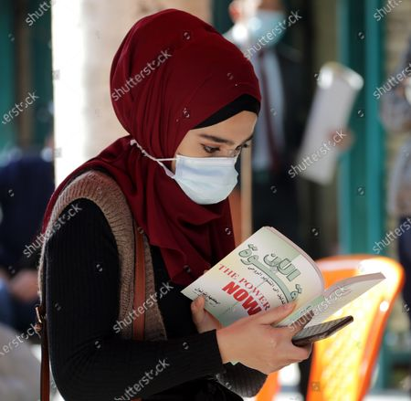 Stock Photo of A woman wears a face mask as she shops at the weekly books market at Al-Mutanabbi Street in central Baghdad, Iraq, 04 December 2020. Iraq needs international assistance to enact its plan to provide its citizens with a free-of-charge Covid-19 vaccine, Iraqi President Barham Salih told the United Nations on 03 December 2020.