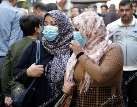 Stock Picture of Women wear face masks as they shop at the weekly books market at Al-Mutanabbi Street in central Baghdad, Iraq, 04 December 2020. Iraq needs international assistance to enact its plan to provide its citizens with a free-of-charge Covid-19 vaccine, Iraqi President Barham Salih told the United Nations on 03 December 2020.