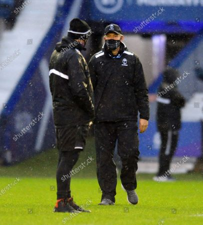 Richie Gray - Fiji assistant coach chats with head coach Vern Cotter in the pouring rain at Murrayfield Stadium.