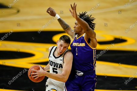 Iowa guard CJ Fredrick drives past Western Illinois guard Anthony Jones, right, during the first half of an NCAA college basketball game, in Iowa City, Iowa