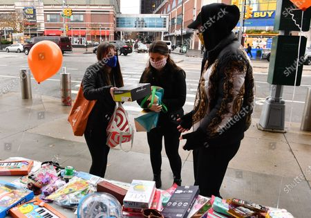 Stock Image of People drop off toys at a toy/gift drive organized by activist/designer Jason Christopher Peters(right) outside of The Barclays Center in Brooklyn, New York City.