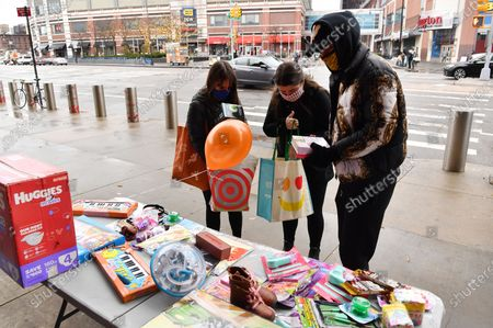 People drop off toys at a toy/gift drive organized by activist/designer Jason Christopher Peters(right) outside of The Barclays Center in Brooklyn, New York City.