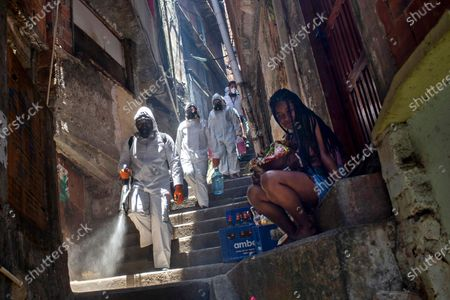 Volunteers spray disinfectant in an alley to help contain the spread of the new coronavirus, at the Santa Marta slum in Rio de Janeiro, Brazil, . Volunteers who have been sanitizing the narrow alleyways and homes in the shantytowns in Rio provided this service for the last time on Saturday. The volunteers led by Thiago Firmino said they have run out funds even as the number of COVID-19 infections are spiking again in the city