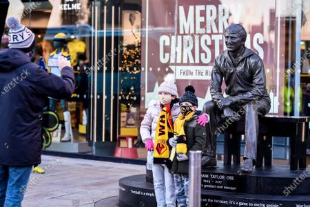 Supporters take a picture with the Graham Taylor statue outside Vicarage Road Stadium.; Vicarage Road, Watford, Hertfordshire, England; English Football League Championship Football, Watford versus Cardiff City.