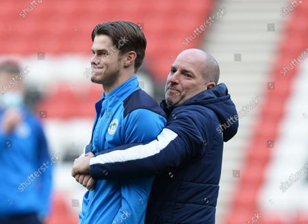 Stock Image of Tom Pearce of Wigan Athletic messes around with Dr Jonathan Tobin the club doctor