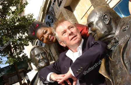 Ray Gosling and Floella Benjamin with statues of Franklin D. Roosevelt and Winston Churchill.