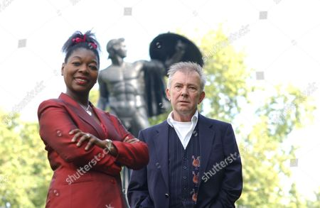 Ray Gosling and Floella Benjamin standing by statue of Achilles in Hyde Park, London.
