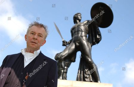 Presenter Ray Gosling Standing by statue of Achilles in Hyde Park, London.